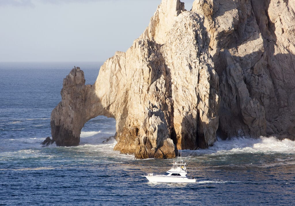 The boat passing by famous rock arch of Cabo San Lucas resort town (Mexico).